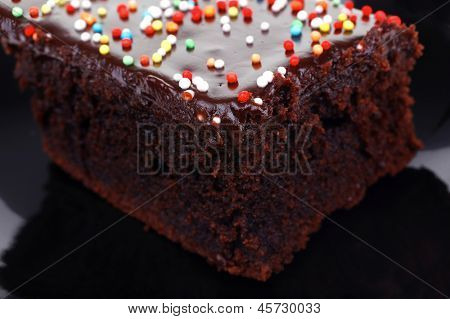 sweet food : chocolate cake coated with chocolate on black saucer isolated over white background
