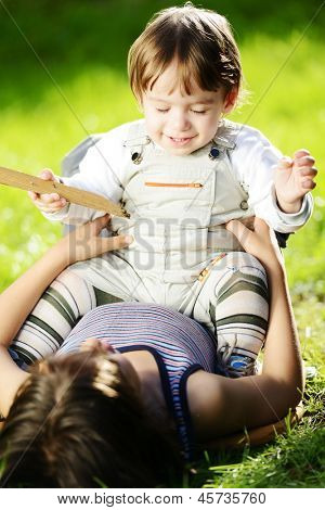 Cute smiling playful baby having fun time with bigger brother outside in summer park