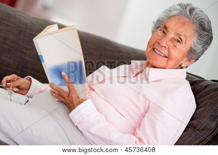Elder woman reading a book relaxing at home