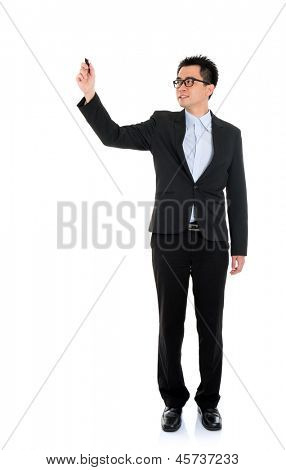 Full body picture of an Asian business man writing with marker standing isolated on white background