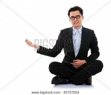 Full body portrait of young happy smiling cheerful Asian business man hand showing blank copy space sit on floor, isolated over white background