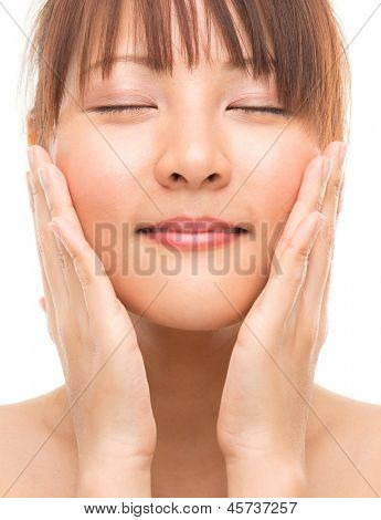 Facial massage. Asian skincare woman pampering face skin, skin care refreshing concept. Facial close up of beautiful mixed race Asian. Girl isolated on white background