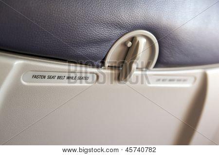 """飞机的座位,聚焦""""系好安全带""""的警告标签里面"""