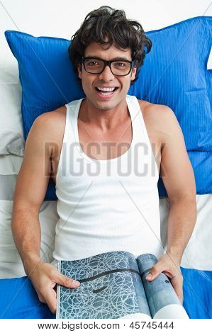 Happy Young Man With Glasses In Bed