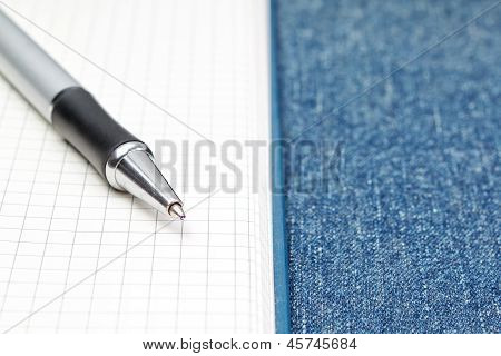 Notepad Open And Pen. On A Material Of Jeans.