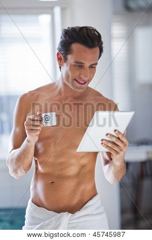 Man Wrapped In Towel Holding A Cup Of Coffe And Tablet