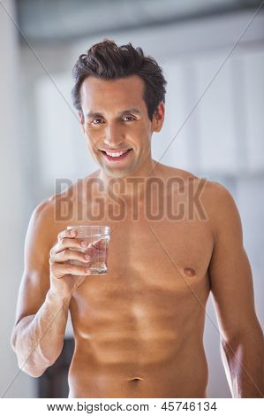 Man Wrapped In Towel Holding A Glass Of Water