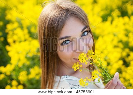 Cheerful Girl Smelling Yellow Wildflower
