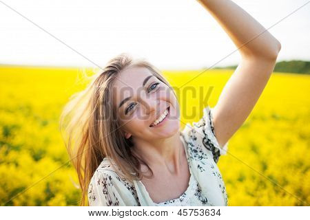 Beautiful Woman Among Yellow Flowers In A Field