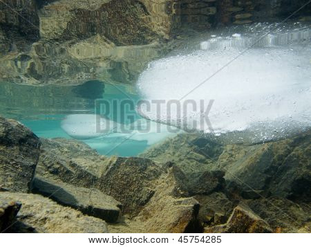 Ice floats in shallow lake with rock reflections