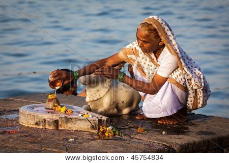 MAHESHWAR, INDIA - APRIL 26: Indian woman performs morning pooja on sacred river Narmada ghats on April 26, 2011 in Maheshwar, Madhya Pradesh, India. To Hindus Narmada is one of 5 holy rivers of India