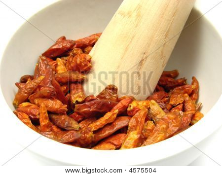 Pestling Dried Red Hot Chili Pepper In A Bowl Of Chinaware