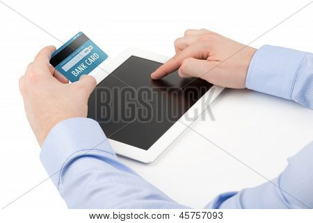 Man's Hand Holding A Credit Card Over A Tablet Computer And The Other Hand Touching The Screen.