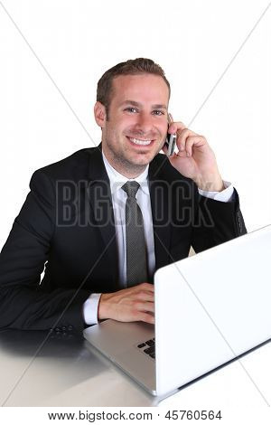 Business man using his laptop while on the phone