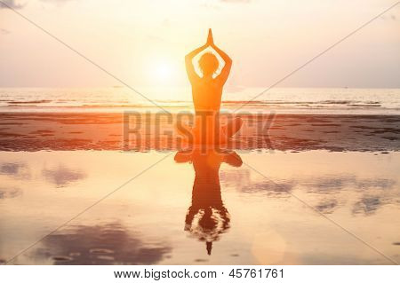 Yoga woman sitting in lotus pose on the beach during sunset, with reflection in water (in bright colors)