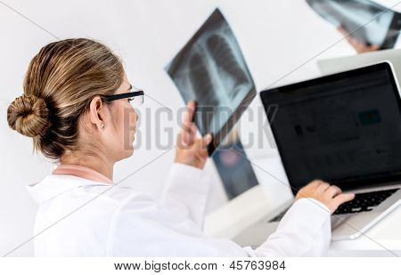 Doctor working at the hospital on a laptop and holding x-ray