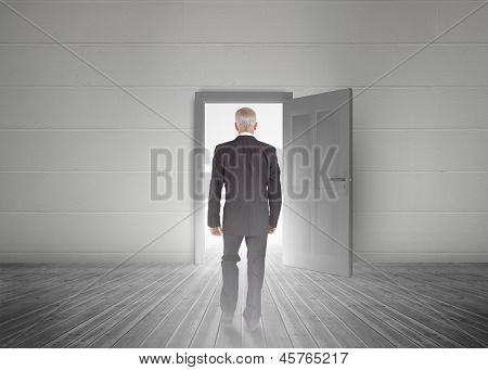 Businessman walking towards door showing light in a dull grey room
