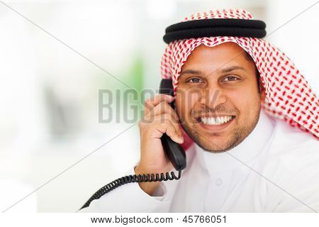 smiling middle eastern man answering telephone in office