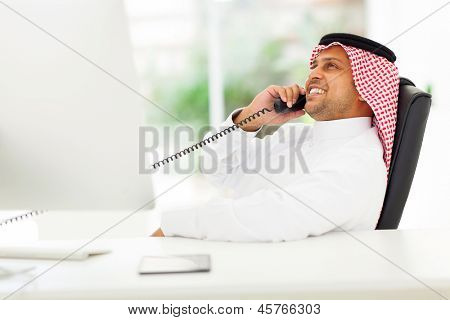 cheerful arabian corporate worker talking on the landline phone