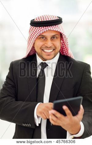 happy arab businessman browsing internet on his tablet computer