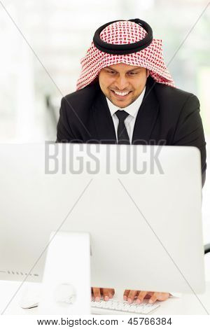 happy middle eastern businessman working on the computer
