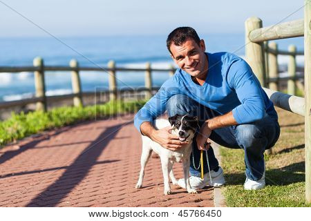 cheerful young man with his pet dog at the beach