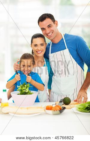 beautiful young family cooking in kitchen at home