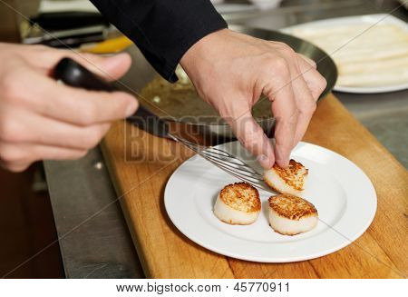 Chef is serving seared scallops on plate