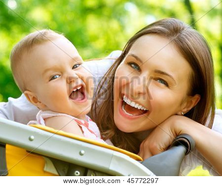 Laughing Mother And Baby outdoors. Nature. Beauty Mum and her Child playing in Park together. Outdoor Portrait of Smiling and Happy family. Joy. Mom and Baby