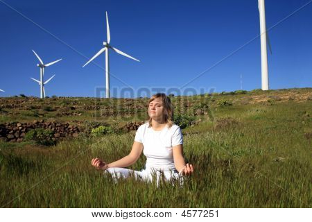 Young Blond Woman Doing On The Grass On A Wind Farm Beneath Eolic Generator