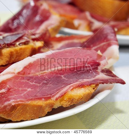 closeup of a some plates with spanish tapas of serrano ham served on sliced bread, on a set table of a restaurant