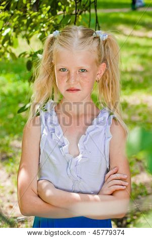 Blonde Girl Standing In A Garden With Hands Clasped, Looking Into The Camera And Smirks