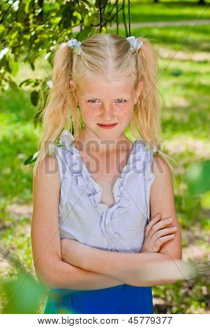 Blonde Girl Standing In The Garden With Hands Clasped, Conceives Something Sly