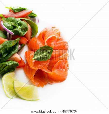 Salted salmon with fresh green salad and lime on white