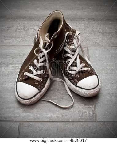 Sneakers In Brown & White On A Stone Floor