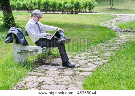 Businessman using laptop while sitting on a bench