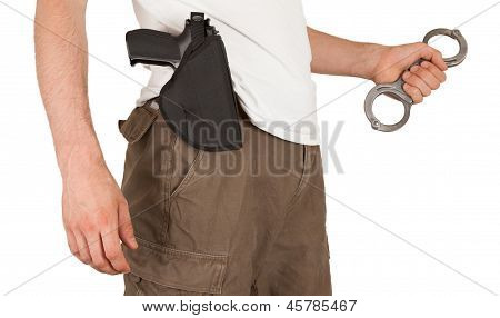 Close-up Of A Man With A Gun And Handcuffs