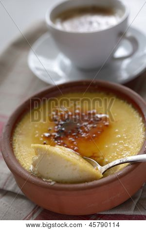 Crema catalana in a pot and a cup of coffee. Selective focus on a middle of dessert