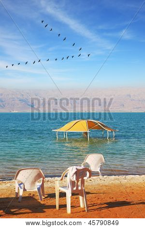 Beautiful sunny day at a beach resort. The Dead Sea, beach umbrellas and deckchairs waiting for tourists