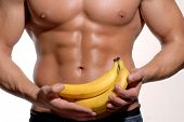 stock photo of abdominal muscle  - Shaped and healthy body man holding a fresh bananas - JPG