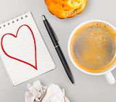 love letter. crumpled wads, notebook with heart picture and cup