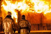 Arson or nature disaster - firefighters at burning fire flame on wooden house roof. Inscription on b