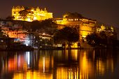 stock photo of mughal  - City Palace and Pichola lake at night - JPG