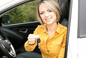 Portrait of happy beautiful woman with car key, sitting in the car