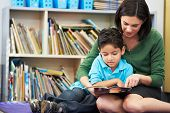 stock photo of pupils  - Elementary Pupil Reading With Teacher In Classroom - JPG
