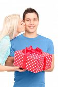 Young woman kissing a man with a present box, isolated on white background