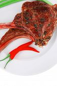 meat savory : grilled beef ribs served with green chives and raw red chili peppers on white dish iso