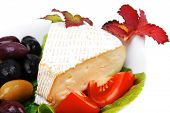 aged camembert cheese on green salad in white platter with olives and tomato isolated over white bac
