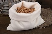Grains in sack on wooden background