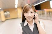 Portrait of young business woman stand and talk on mobile phone in the MRT station, Taipei, Taiwan,